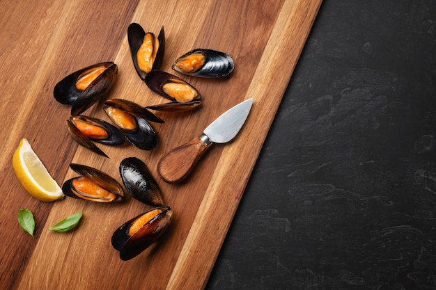 Seafood mussels with basil leaves on wooden board and stone table. top view with place for your text.