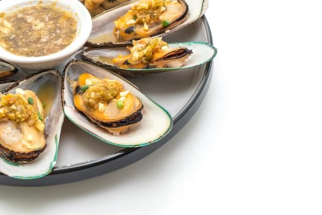 Мидии из морепродуктов с острым соусом из морепродуктов, изолированные на белом фоне