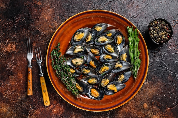 접시에 와인 소스와 백리향을 곁들인 해산물 홍합. 어두운 배경입니다. 평면도.