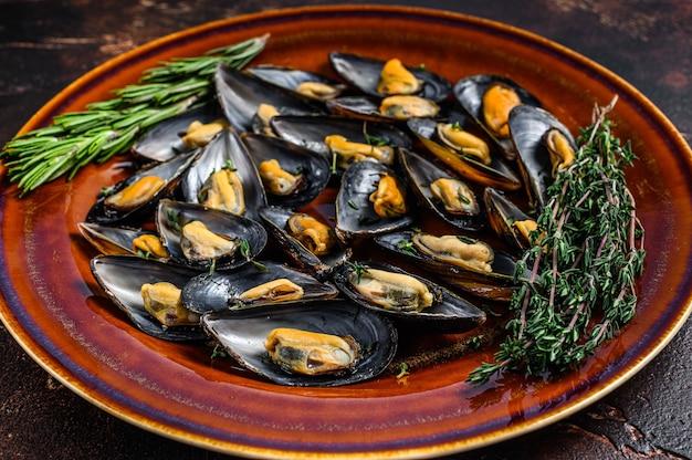 접시에 와인 소스와 백리향을 곁들인 해산물 홍합
