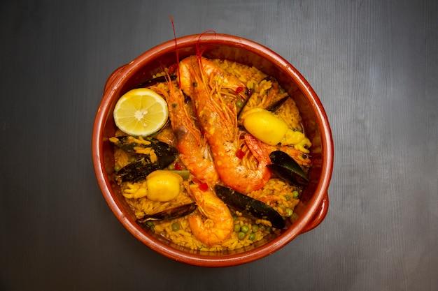 Seafood paella in ceramic bowl on dark wood. rice with seafood.