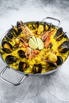 Seafood paella in the fry pan with prawns, shrimps, octopus and mussels