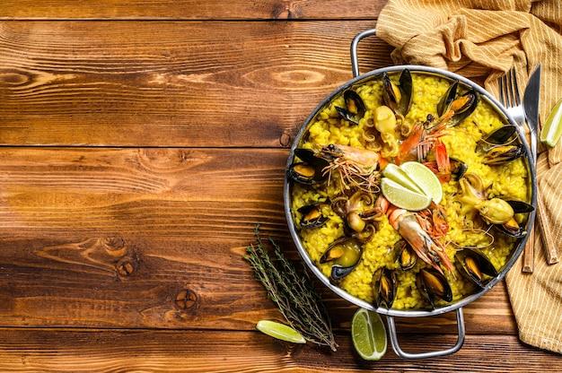Паэлья из морепродуктов в сковороде с креветками, креветками, осьминогами и мидиями. деревянный фон. вид сверху. скопируйте пространство.