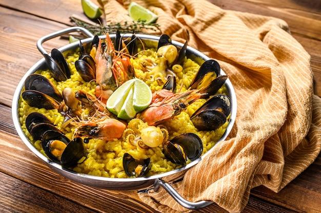 Паэлья из морепродуктов в сковороде с креветками, креветками, осьминогами и мидиями. деревянный фон. вид сверху.