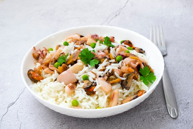 Паэлья с морепродуктами в белой тарелке и рис с вилкой с мидиями кальмары с креветками и петрушкой