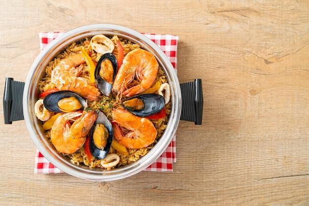 エビ、アサリ、ムール貝のサフランライスを添えたシーフードパエリア-スペイン料理のスタイル