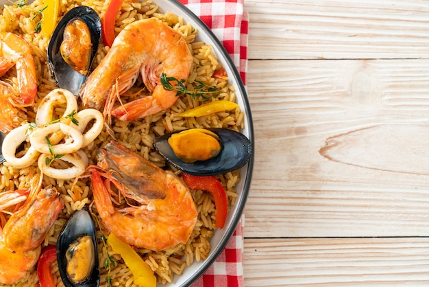 Seafood paella with prawns, clams, mussels on saffron rice - spanish food style