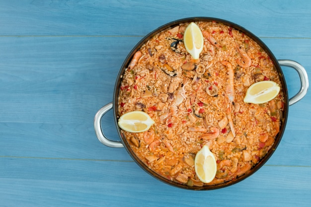 Seafood paella on a wooden blue background