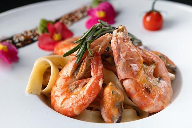 Креветки с мидиями и пастой из морепродуктов на белой тарелке