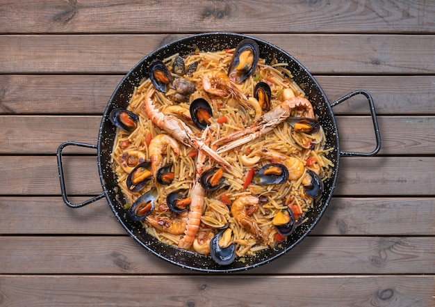 Паэлья с пастой из морепродуктов, испанская кухня на деревянных фоне, вид сверху
