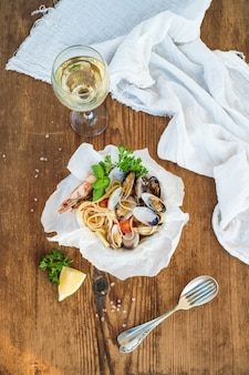 Seafood pasta. spaghetti with clams and shrimps in bowl, glass of white wine over rustic wood  table