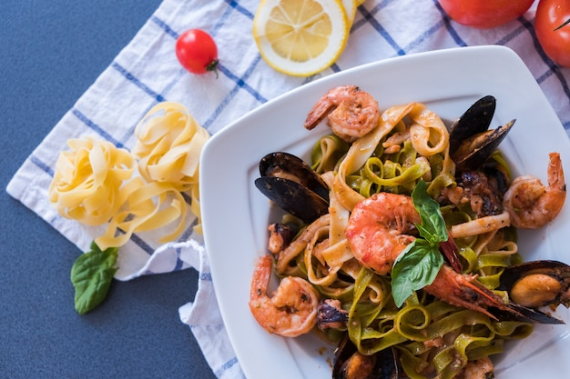 Seafood pasta with mussels and shrimp on white plate. spaghetti on blue background