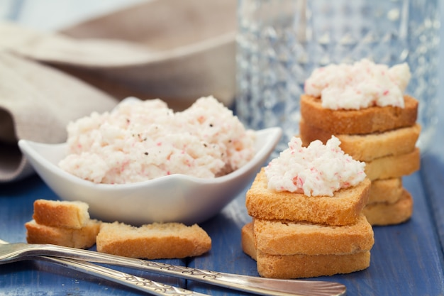 Seafood pate with toasts and glass of water on blue background