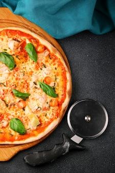어두운 테이블 상단과 피자 칼에 새우와 토마토와 해산물 피자.