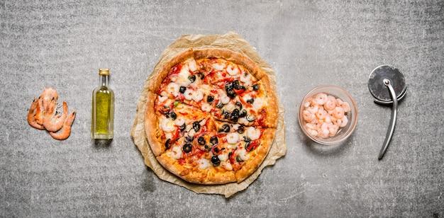 새우와 토마토가 들어간 해산물 피자. 돌 테이블에.