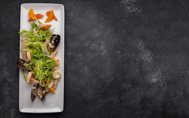 Seafood on a plate, mussels, scallop, shrimp, squid, with salad mix on a dark background