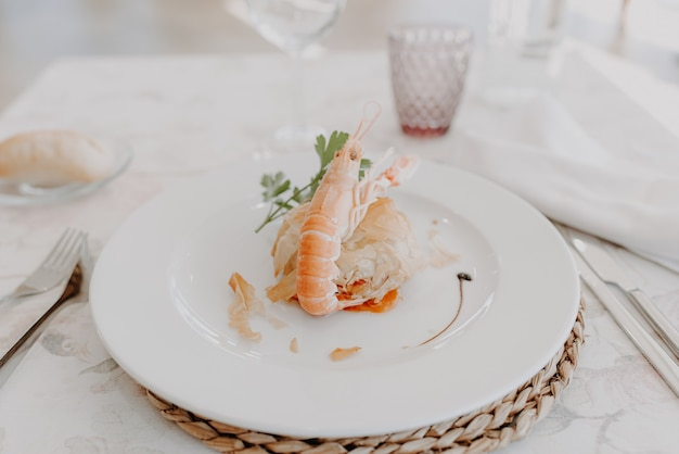Seafood plate with a cooked norway lobster served at an event, added film grain.