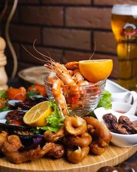 Тарелка с морепродуктами с креветками, мидиями, подается с лимоном
