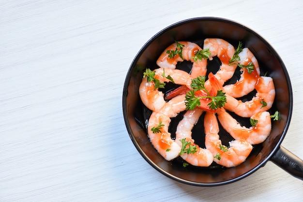 새우 새우 바다 미식가와 해산물 접시 팬에 소스 허브와 향신료와 함께 요리 저녁 식사 테이블을 장식