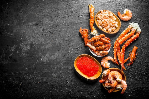 Seafood. plates with boiled crayfish, shrimp, crab and caviar. on black rustic