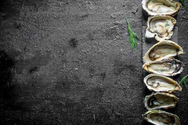 Морепродукты. сырые открытые устрицы на каменной подставке. на черном деревенском
