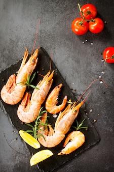 Морепродукты сырые креветки со специями, помидорами и лимоном на грифельной доске. вид сверху.