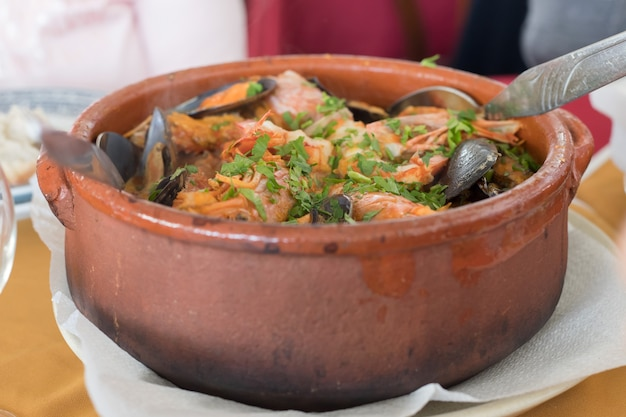 Seafood rice in brown ceramic pot in restaurant