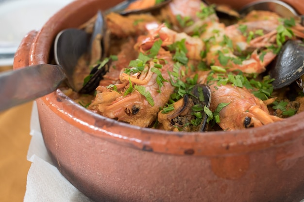 Рис с морепродуктами в коричневом керамическом горшке в ресторане