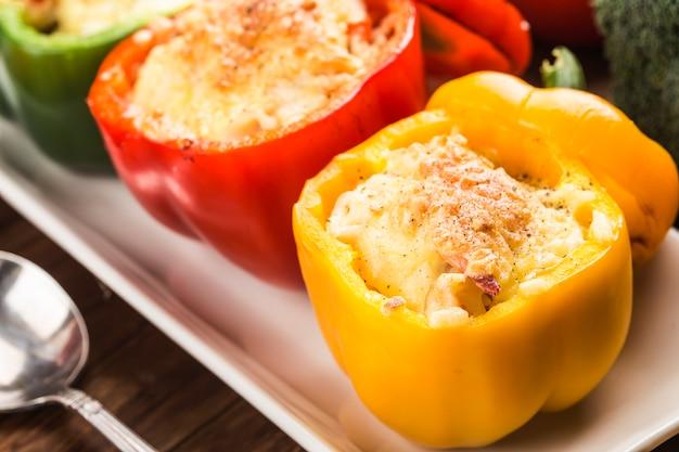 Riso ai frutti di mare con formaggio, peperoni ripieni di riso e carne macinata. .pepe verde alla griglia con formaggio