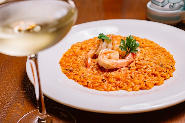 Seafood risotto with tomato sauce garnished with shrimp