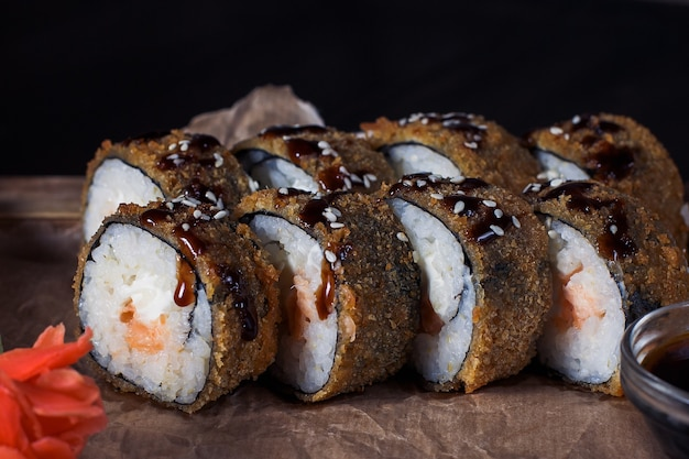 Seafood rolls on a wooden tray, beautiful serving, dark background.
