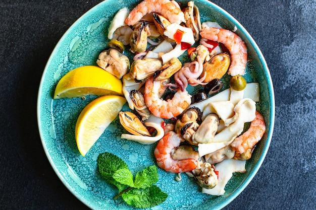 Ассорти салатов из морепродуктов на синей тарелке