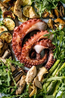 Seafood salad. coocked grilled tentacles of octopus, sardines and mussels on blue ceramic plate served with arugula salad, zucchini and asparagus over blue texture surface. top view. close up