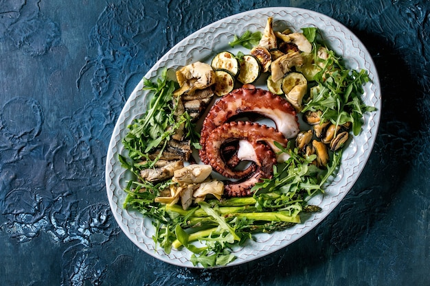 Seafood salad. coocked grilled tentacles of octopus, sardines and mussels on blue ceramic plate with arugula salad, zucchini and asparagus over blue texture surface. top view, flat lay. copy space