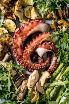 Салат из морепродуктов. жареные на гриле щупальца осьминога, сардин и мидий на синей керамической тарелке, подаваемые с салатом из рукколы, цукини и спаржей на синей текстурной поверхности. вид сверху. закрыть вверх