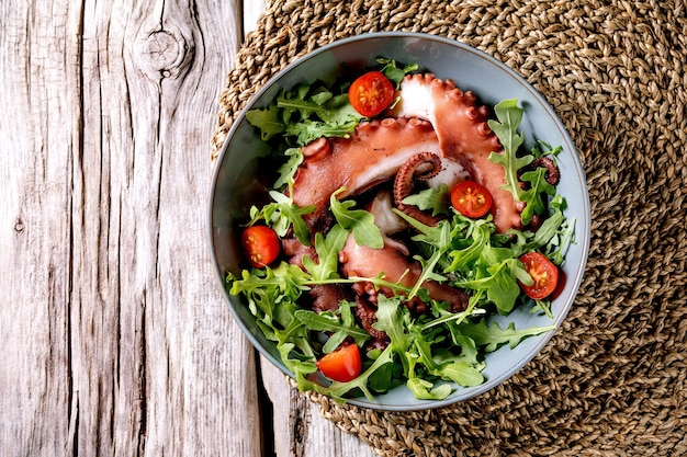 Seafood salad. coocked tentacles of octopus on blue ceramic plate served with rocket leaf aragula and cherry tomato salad over grey wooden surface and wicker lining. top view, flat lay. copy space