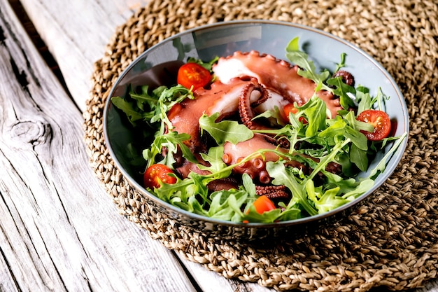 Seafood salad. coocked tentacles of octopus on blue ceramic plate served with rocket leaf aragula and cherry tomato salad over grey wooden surface and wicker lining.