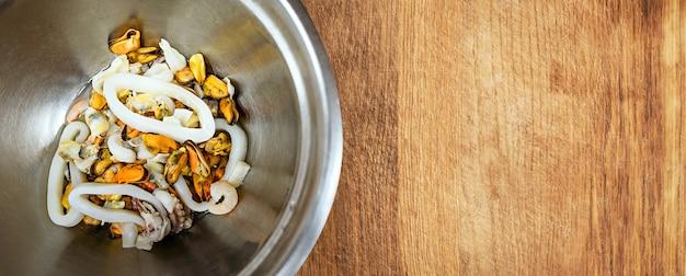 Салат из морепродуктов в металлической миске с пустым пространством для текста