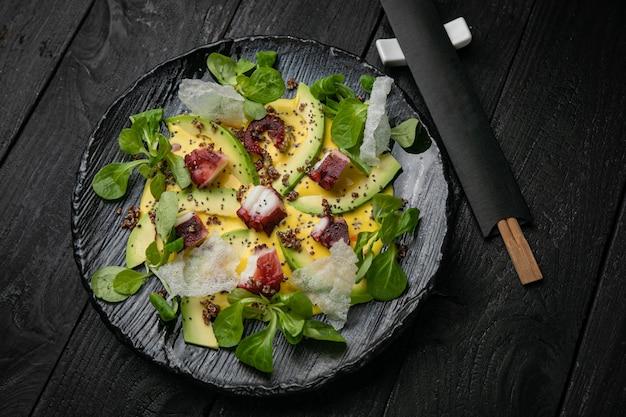 Салат из морепродуктов на темной тарелке и деревянном столе. осьминога готовит шеф-повар
