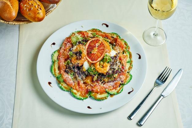 Салат из морепродуктов на белой тарелке с ресторанной подачей. салат с авокадо, креветками и лососем и сладким соусом. здоровый образ жизни.