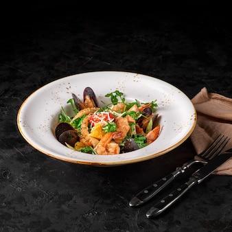 Салат из морепродуктов или закуска из креветок, мидий, кальмаров и других ингредиентов на черном фоне.