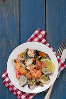 Seafood salad on plate on blue wooden