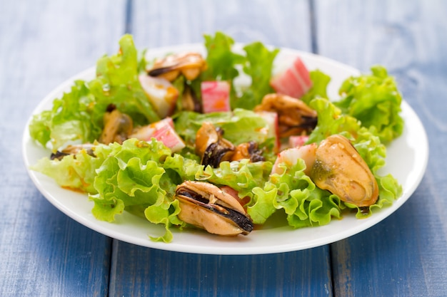 Seafood salad on white dish on blue background