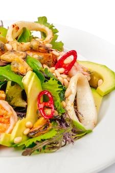 Салат из морепродуктов с авокадо и зеленью на белом фоне