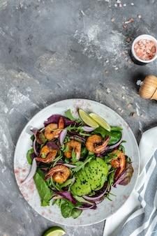 Салат из морепродуктов с авокадо и креветками. вкусный овощной микс из листьев, креветки на гриле. здоровая пища. вертикальное изображение, место для текста.