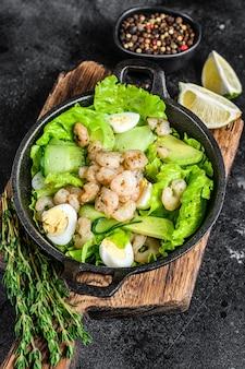 구운 새우 새우, 계란, 아보카도, 오이를 팬에 담은 해산물 샐러드.