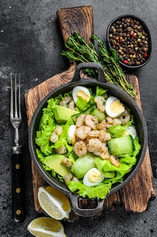 Seafood salad with grilled shrimps prawns, egg, avocado and cucumber in a pan. dark wooden background. top view.