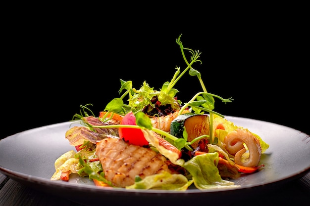 イカのグリル、トウモロコシ、ニンジン、トマト、レタス、灰色の皿のシーフードサラダ