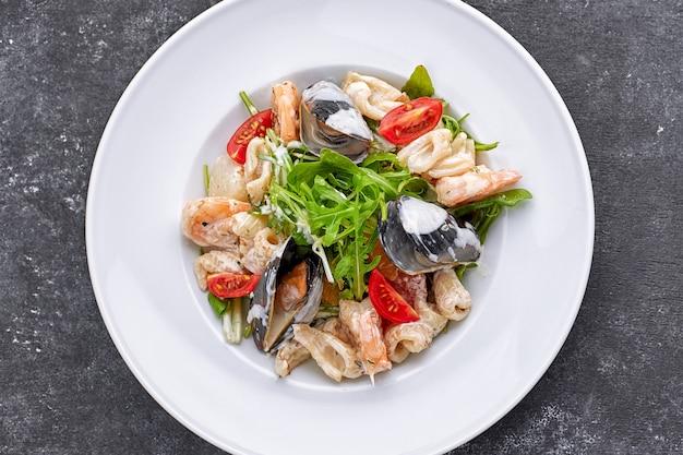 Салат из морепродуктов с мидиями, кальмарами, креветками, на круглой белой тарелке, на сером фоне