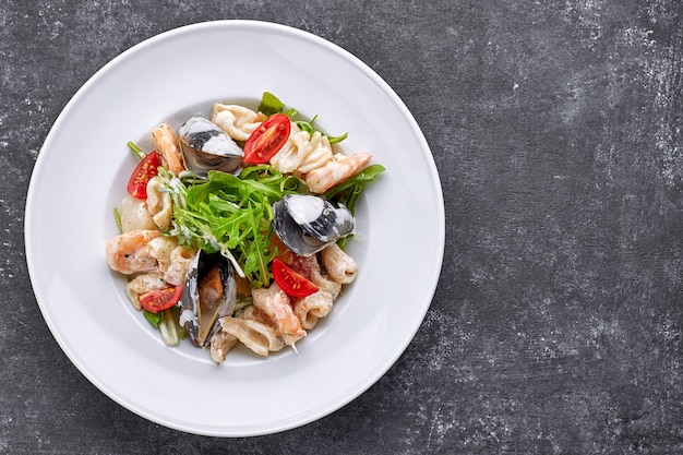 Seafood salad with mussels, squid, shrimp, on a round white plate, on a gray background